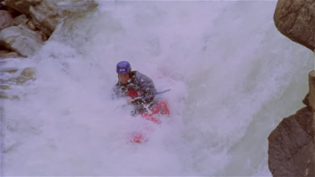 Slow motion man whitewater kayaking through extreme rapids and flipping over in kayak / Lake Creek, Colorado Rockies