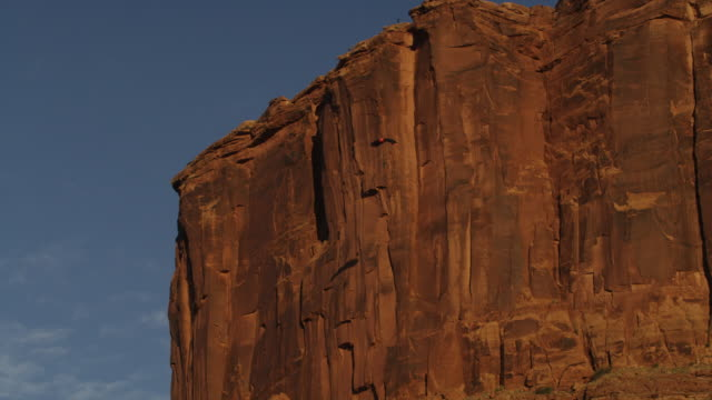 Slow motion, man with parachute glides near cliffs