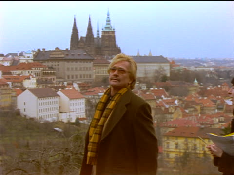 slow motion man + woman pointing up + talking / prague buildings in background / czech republic - フラッチャニ城点の映像素材/bロール