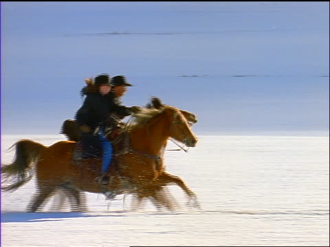 slow motion pan man + woman riding galloping horses through deep snow on plain / silverthorne, co - cowgirl stock videos & royalty-free footage