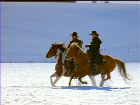 slow motion pan man + woman riding galloping horses through deep snow on plain / silverthorne, co - galoppieren stock-videos und b-roll-filmmaterial