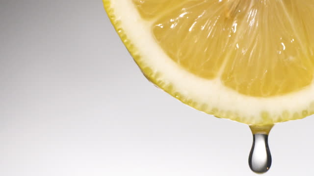 vídeos de stock e filmes b-roll de slow motion: many liquid drop from lemon slice on white - juicy