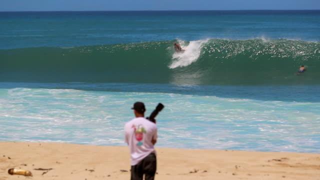 vídeos de stock, filmes e b-roll de slow motion many surfers & bodyboarders in the ocean & one catching a wave - pipeline wave