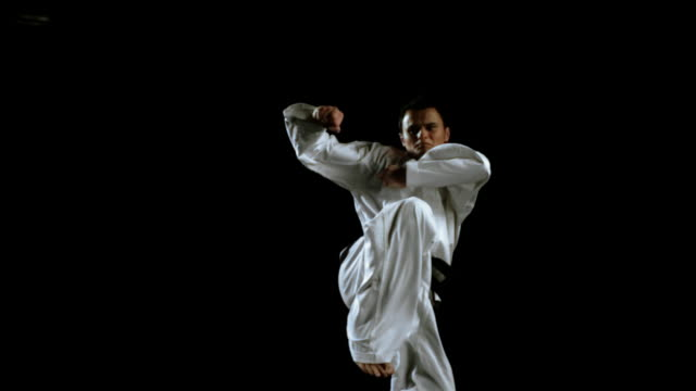 slow motion martial artist jumping and kicking in air - kicking stock videos & royalty-free footage