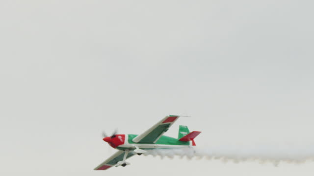 slow motion medium close up single engine, single seat, propeller, light weight aircraft trailing smoke, flies toward the ground, then loop-the-loop. - propeller video stock e b–roll