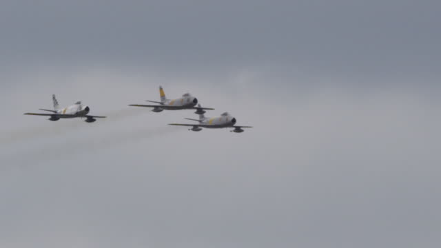 Slow motion medium close up three F-86 Sabre US Air Force military fighter jets fly in tight formation toward and past camera.