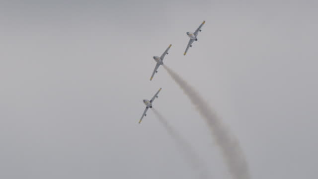 Slow motion medium close up three F-86 Sabre US Air Force military fighter jets fly in tight formation in a loop to loop.