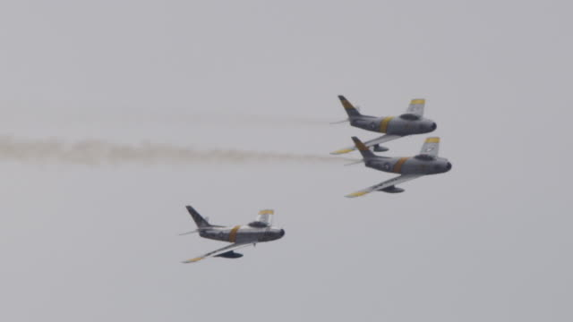 Slow motion medium close up three F-86 Sabre US military Air Force military fighter jets fly in tight formation banking toward camera.