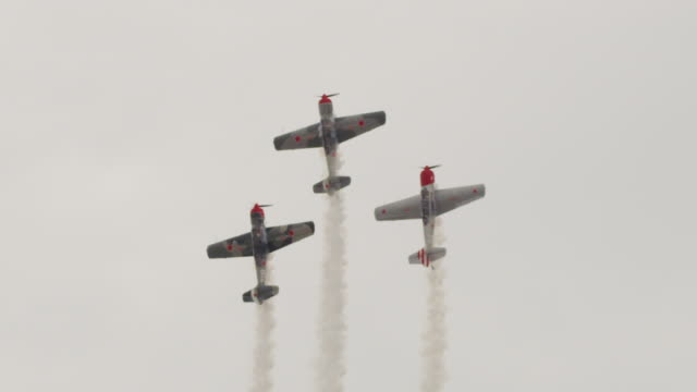 slow motion medium close up three soviet yak-52 military propeller aircraft fly in tight formation and trail smoke during a loop-the-loop stunt. - propeller video stock e b–roll