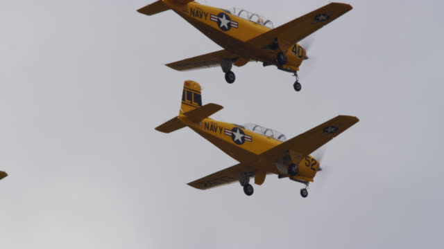slow motion medium close up two us navy military stunt airplanes fly past camera in tight formation. - airshow stock videos & royalty-free footage