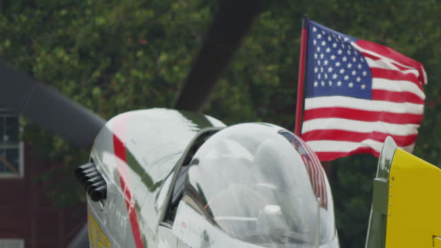 Slow motion medium close up US military fighter prop plane taxis away from camera , cockpit open, American flag flying; shot