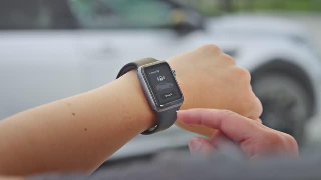 vídeos y material grabado en eventos de stock de slo mo ld mujer tocando su reloj inteligente para bloquear su coche - cerrar con llave