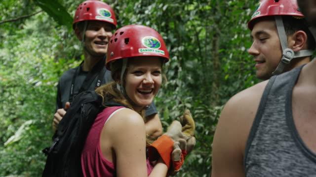 slow motion medium panning shot of zipliners talking in rain forest / quepos, puntarenas, costa rica - puntarenas stock-videos und b-roll-filmmaterial