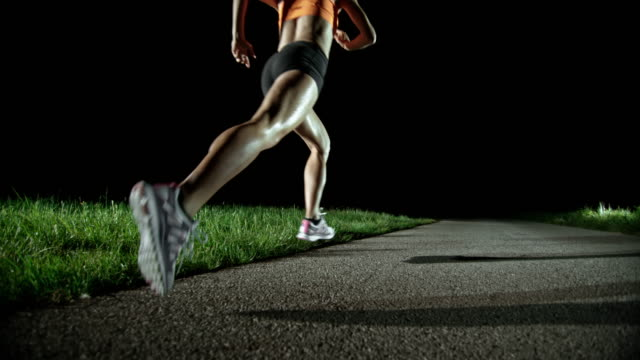 slo mo pan female marathon runner running at night - sportsperson stock videos & royalty-free footage