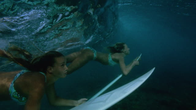 Slow motion medium shot 2 women in matching bikinis approach surface of water on surfboards / Tahiti