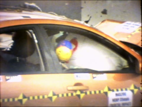 slow motion medium shot 35mph frontal barrier impact test on 2004 four-door nissan maxima with crash test dummies - crash test stock videos & royalty-free footage