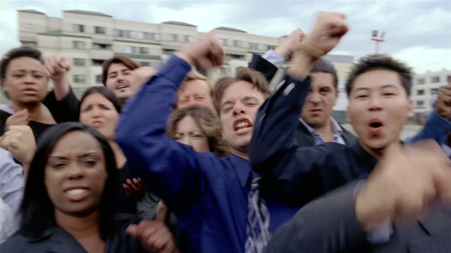 stockvideo's en b-roll-footage met slow motion medium shot angry crowd glowering and shaking fists at camera - woede