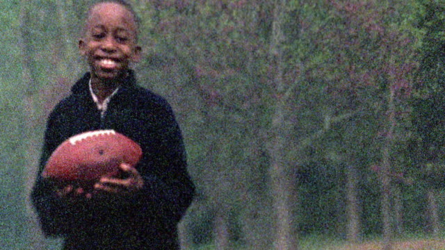 Slow motion medium shot Black boy flipping football in hands and smiling standing outdoors / Missouri