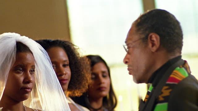 vídeos y material grabado en eventos de stock de slow motion medium shot black bride and groom / pan to clergyman speaking - sacerdote