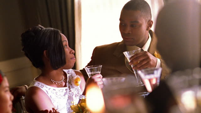 Slow motion medium shot Black bride and groom toasting at crowded banquet table