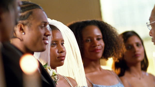 slow motion medium shot black clergyman administering wedding vows / pan to black couple kissing - wedding vows stock videos & royalty-free footage