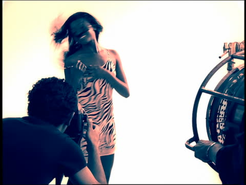 Slow motion medium shot Black model posing in studio for photographer and fan operator in foreground