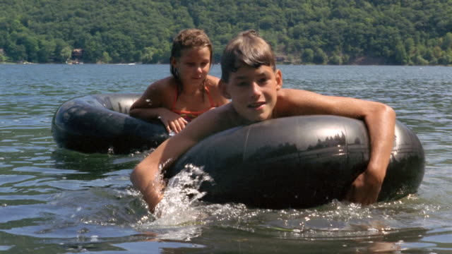 slow motion medium shot boy and girl floating on inner tubes in lake/ boy looking at cam/ canandaigua lake, new york - 水泳用浮き輪点の映像素材/bロール
