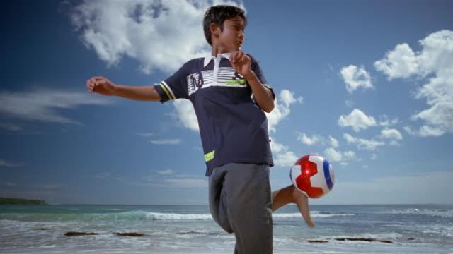 Slow motion medium shot boy kicking soccer ball on beach as tide rolls in/ Bali, Indonesia