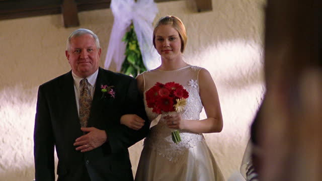 Slow motion medium shot bride and her father walking down aisle