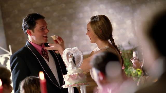 Slow motion medium shot bride feeding groom piece of wedding cake