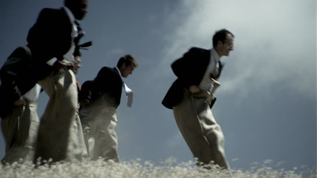vidéos et rushes de slow motion medium shot businesspeople competing in sack race in field - concours