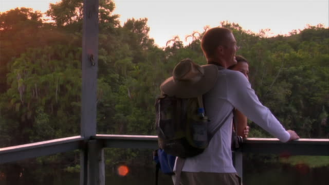 slow motion medium shot couple looking out on river from bridge/ the amazon, brazil - zaino da montagna video stock e b–roll