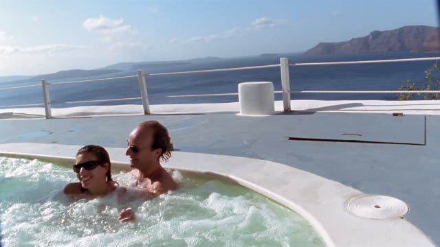 slow motion medium shot couple relaxing in hot tub with aegean sea in background / kissing and laughing / santorini, greece - bagno caldo video stock e b–roll
