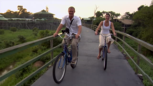 slow motion medium shot couple riding bicycles on footbridge attached to ecolodge/ the amazon, brazil - elevated walkway stock videos & royalty-free footage