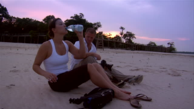 vídeos de stock, filmes e b-roll de slow motion medium shot couple sitting on beach at sunset and drinking water/ the amazon, brazil - água potável