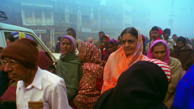 slow motion medium shot crowd of people in robes walking on busy city street with vendors in fog / varanasi, india - indian subcontinent ethnicity stock videos & royalty-free footage