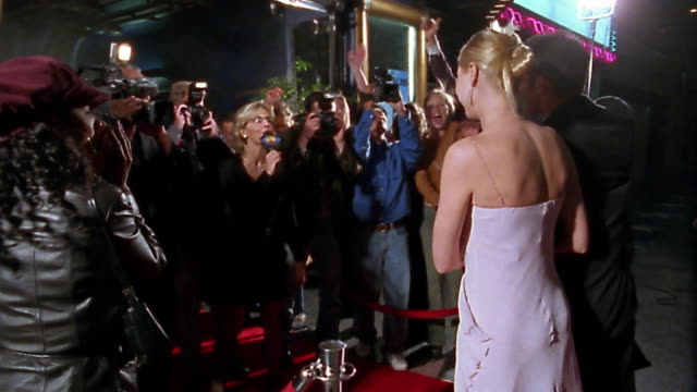 Slow motion medium shot dolly shot famous couple walking on red carpet past groupies, camermen, reporter and photographers