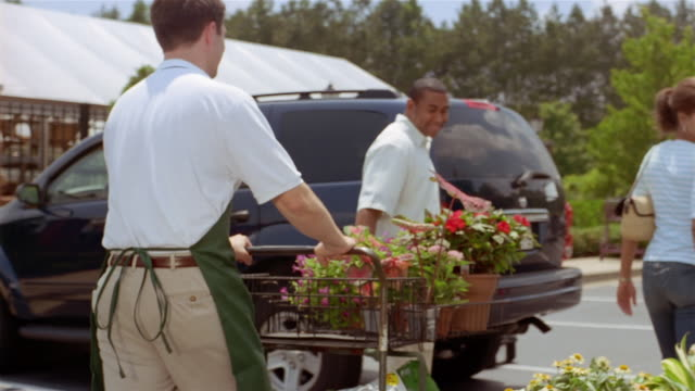 slow motion medium shot employee wheeling cart of plants to couple's car in parking lot of garden center - suv点の映像素材/bロール