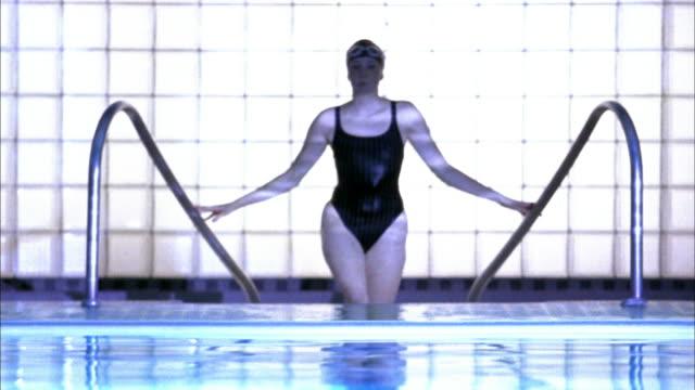 stockvideo's en b-roll-footage met slow motion medium shot female swimmer stepping onto pool deck and lowering goggles - binnenbad