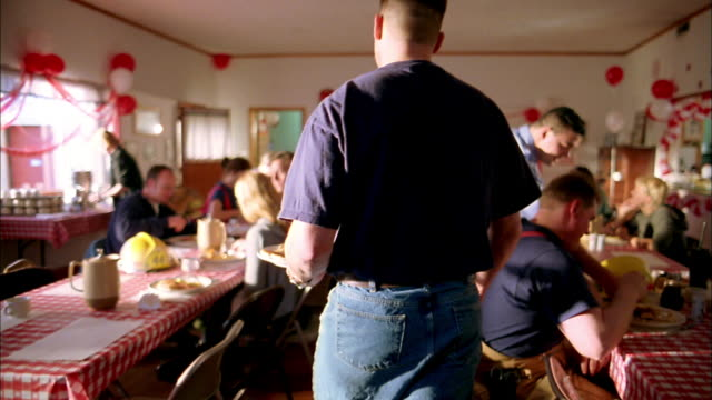 vídeos de stock e filmes b-roll de slow motion medium shot firefighter holding plate of pancakes and sitting down at table w/people eating breakfast - sentar se