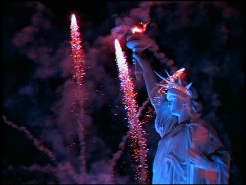 Slow motion medium shot fireworks shooting into sky around Statue of Liberty at night / New York City