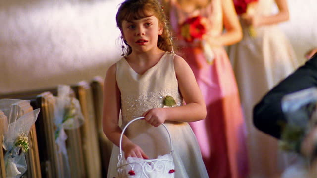 vídeos de stock, filmes e b-roll de slow motion medium shot flower girl walking down aisle dropping rose petals from a basket - dama de honra