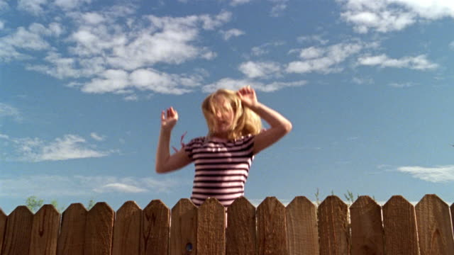 slow motion medium shot girl bouncing up and down behind fence - recinzione video stock e b–roll
