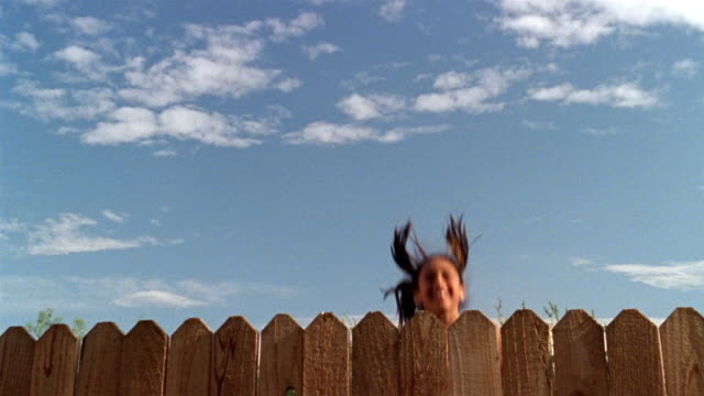 vídeos de stock, filmes e b-roll de slow motion medium shot girl bouncing up and down behind fence - cerca