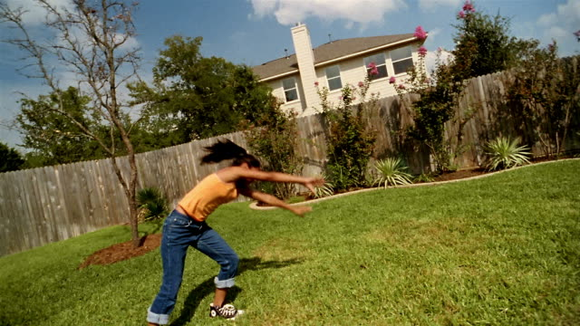 vídeos de stock e filmes b-roll de slow motion medium shot girl doing cartwheels in backyard - jeans