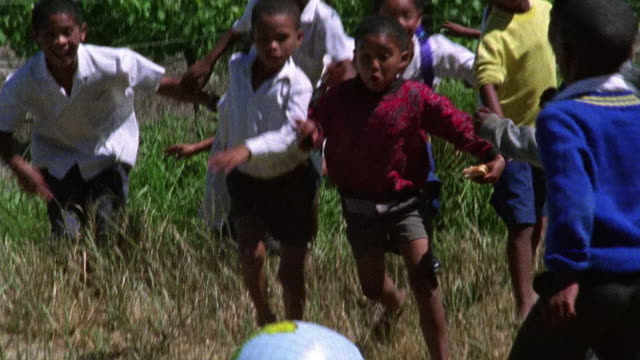 Slow motion medium shot group of barefooted Black children play soccer with inflatable globe outdoors / South Africa