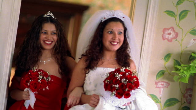 slow motion medium shot hispanic bride and bridesmaid walking through doorway arm in arm - arm in arm stock videos & royalty-free footage