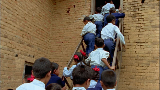 slow motion medium shot large group of small schoolchildren climbing steep stairs to school / nepal - schoolhouse stock videos & royalty-free footage
