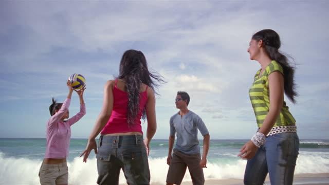 vídeos y material grabado en eventos de stock de slow motion medium shot man and women playing with volleyball on beach/ bali, indonesia - indonesia