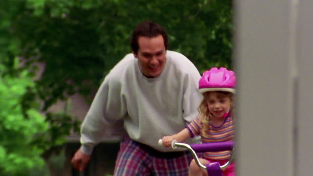Slow motion medium shot man helping small girl learn how to ride bicycle